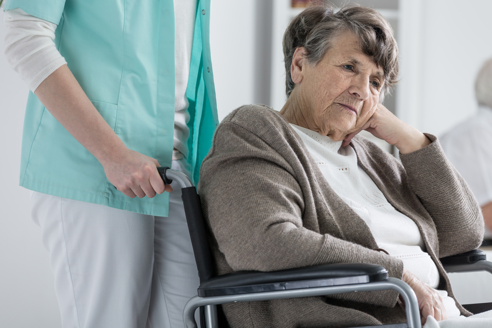 Sad woman in a wheelchair being pushed